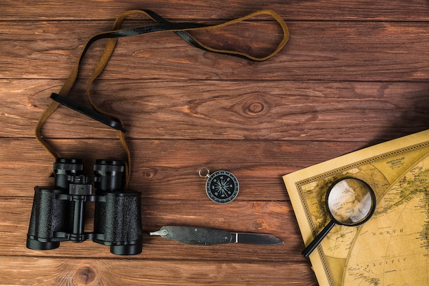 Binocular, compass, and knife with microscope on vintage map