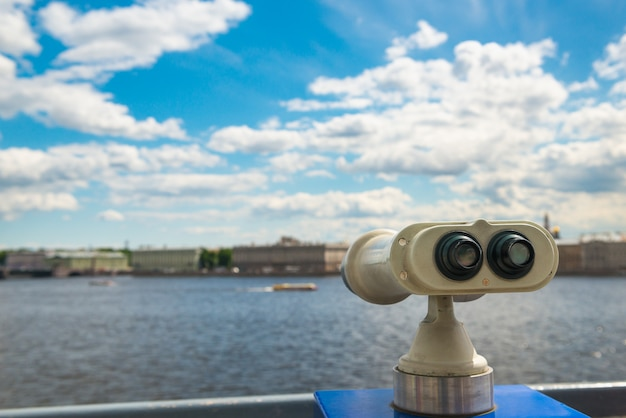 Binocular on viewing platform, selective focus, view of city and sky with clouds.