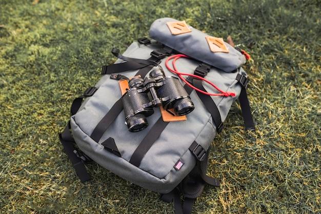 Бинокли и рюкзак на траве