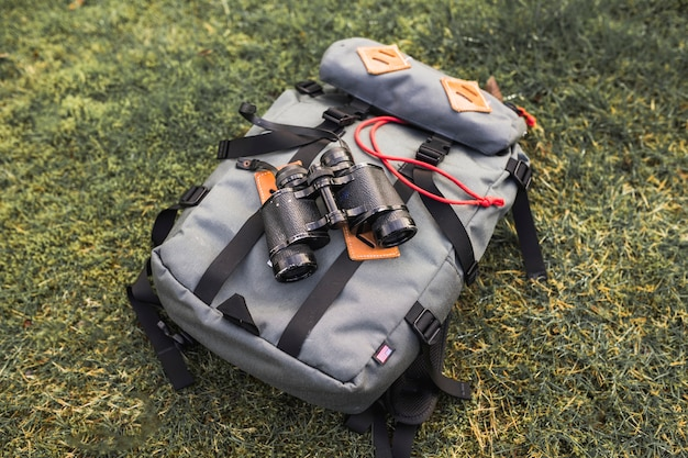 Binoculars and backpack on grass