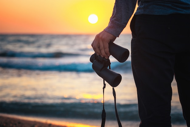 Binoculars in the hands of a man standing on the beach