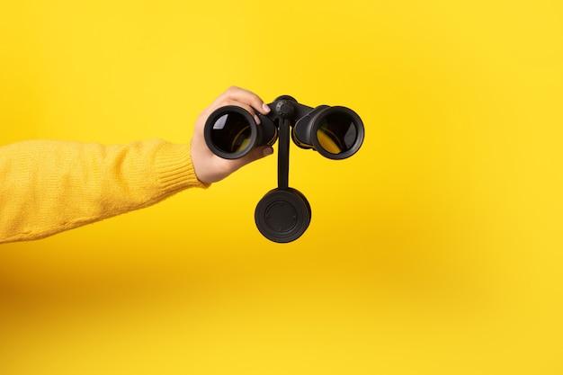 노란색 배경 위에 손에 쌍안경, 찾기 및 검색 개념. 프리미엄 사진