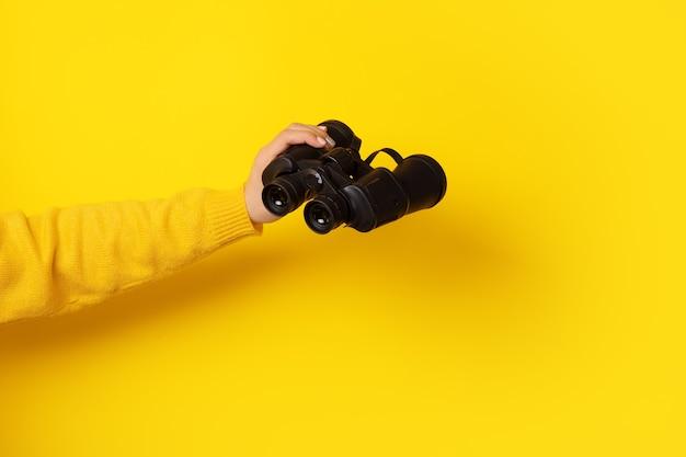 노란색 배경 위에 손에 쌍안경, 찾기 및 검색 개념.