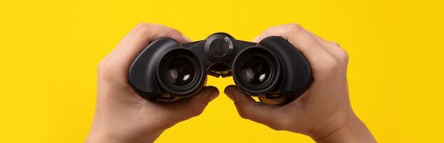 노란색 배경 위에 손에 쌍안경, 찾기 및 검색 개념