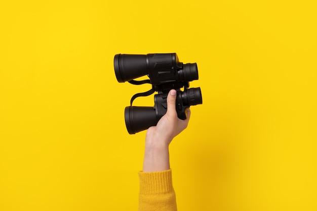 노란색 배경, 검색 개념 위에 손에 쌍안경. 프리미엄 사진