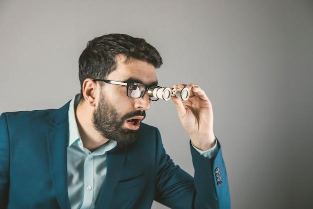 驚いたビジネスマンの手に双眼鏡