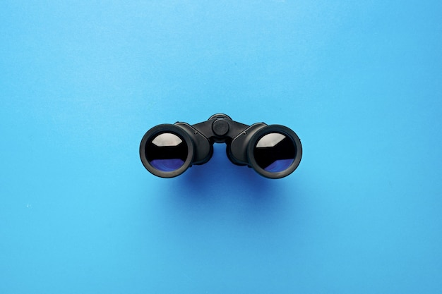 Binoculars on a light blue