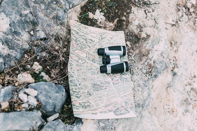 Binoculars and map on rock