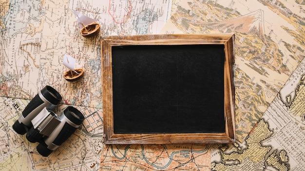 Binoculars near blackboard on maps