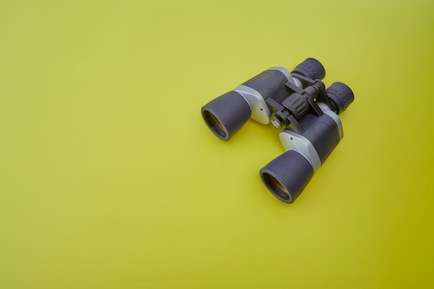 Binoculars silver and gray on yellow background