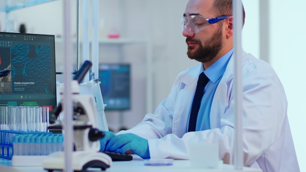 生化学者は、化学実験室で特別なソフトウェアを使用してコンピューター上でウイルス書き込みの兆候をチェックします。ハイテク研究診断を使用してワクチンの進化を調べる医師のグループ