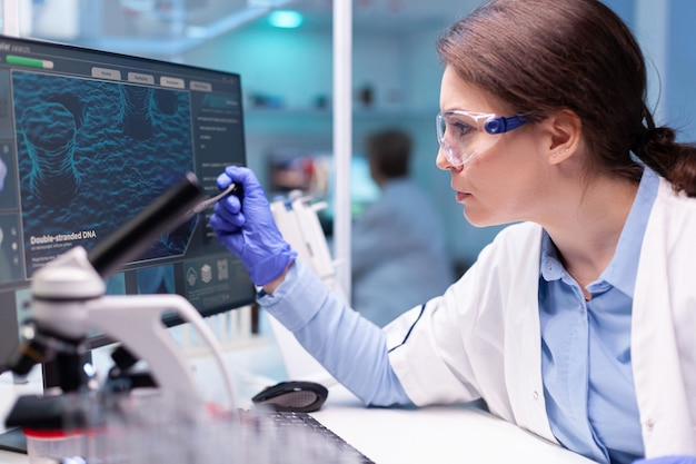 바이러스에 대한 기술을 발견하기 위해 실험실에서 일하는 생화학자 과학자