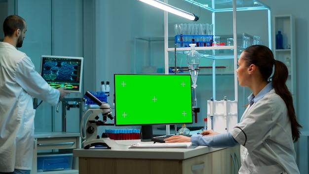 생화학자는 크로마 키 모니터가 있는 녹색 모의 화면 개인용 컴퓨터를 사용하여 실험실의 직장에 앉아 있습니다. 제약 연구 센터의 배경에서 일하는 동료.