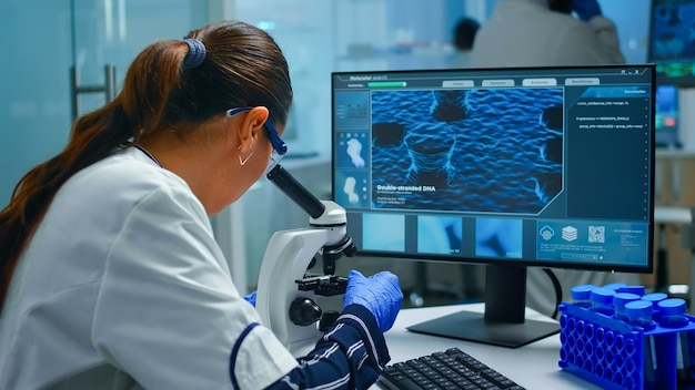 Biochemist using microscope and writing at computer sitting in equipped laboratory. scientist doctor working with various bacteria, tissue, blood samples, pharmaceutical research for antibiotics