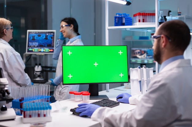 Biochemist working in laboratory using green mock-up screen for biochemistry experiment with chroma key monitor