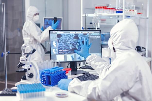 Biochimica in medicina che lavora in una struttura moderna per trovare una cura per il coronavirus vestita con una tuta. ingegneri di laboratorio che conducono esperimenti per lo sviluppo di vaccini contro il virus covid19