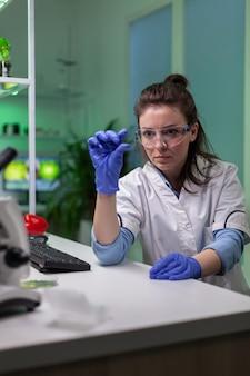 생화학 실험을 위해 현미경을 사용하여 녹색 액체 샘플을 분석하는 생화학 과학자. 제약 실험실에서 일하는 생물학자 여성이 gmo 전문 지식을 발견합니다.