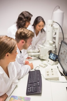 Студенты биохимии, используя большой микроскоп и компьютер