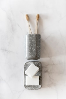 Biodegradable bamboo toothbrushes and naturals soap on marble background