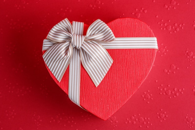 Biodegradable cardboard gift box in the shape of a heart with ribbons on red