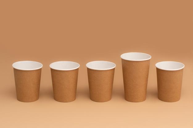 茶色の背景に一列に並んだ生分解性クラフト紙コップ。茶色の紙の使い捨てカップ。ゼロウェイスト