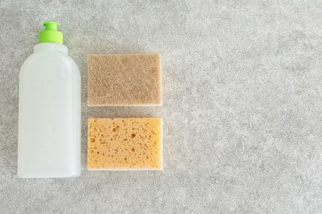 돌 테이블에 생분해성 접시 세척 젤과 거품 스폰지. 청소 및 청결 유지의 개념입니다.