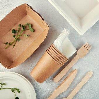 生分解性の使い捨て食器。紙皿、カップ、箱。木製カトラリー。フラットレイ