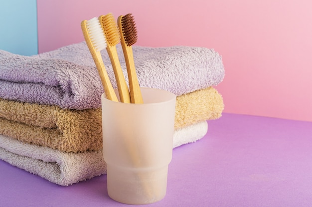 Biodegradable natural bamboo toothbrush in glass witn towels on color pink background.