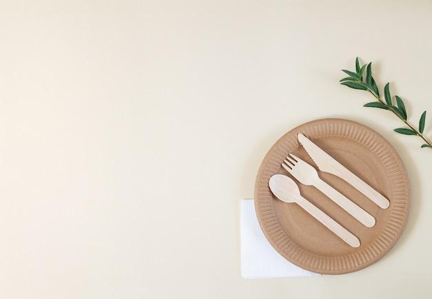 Биоразлагаемая бумажная тарелка со столовыми приборами, салфеткой и зелеными листьями на бежевом фоне, вид сверху.
