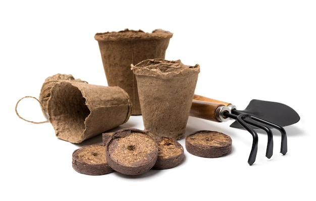 Biodegradable peat pots, peat tablets, garden tools and rope isolated on white background
