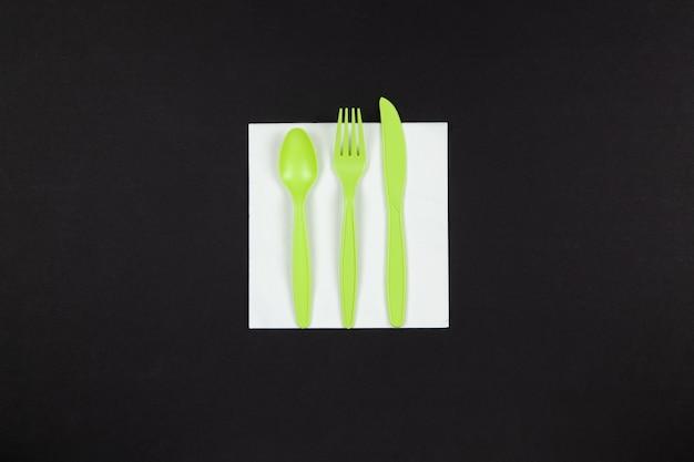 생분해 성 재사용 가능한 재활용 녹색 포크, 숟가락, 옥수수 전분으로 만든 칼은 검은 색 바탕에 흰색 냅킨에 놓여 있습니다.