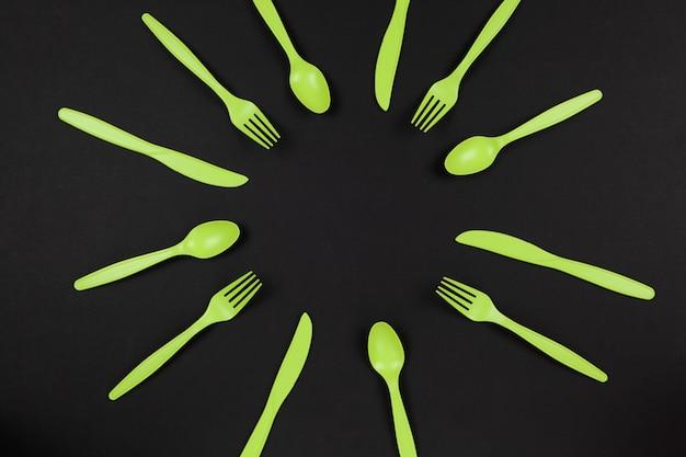 생분해 성 재사용이 가능한 재활용 가능한 녹색 포크, 숟가락, 옥수수 전분으로 만든 칼 또는 검은 색 테이블에 태양이나 꽃처럼 배치 된 귀리. 에코, 제로 폐기물 개념. 평평하다. 수평. 확대.
