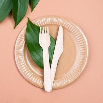 生分解性食器カトラリーとプレート上の葉