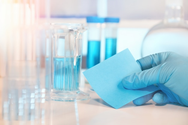 Biological or biochemical lab out of focus, closeup on gloved hand, space