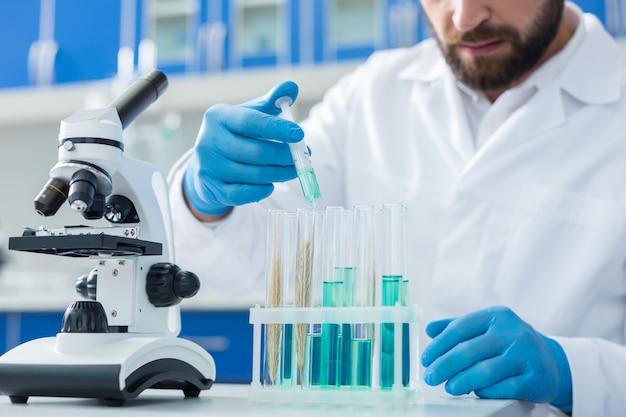 생물 공학. 현미경 근처의 테이블에 생물학적 샘플이 서있는 테스트 튜브의 선택적 초점