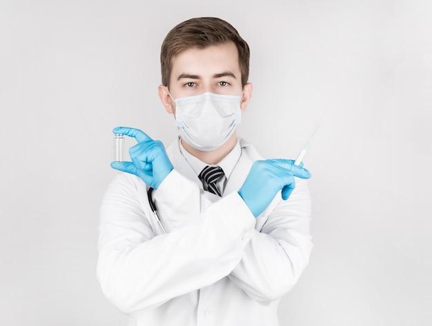 Биологическая опасность. эпидемия китайского коронавируса. мужчина в медицинском халате и маске держит шприц для инъекций и вакцину. вакцина против гриппа, коронавируса, лихорадки эбола, туберкулеза.