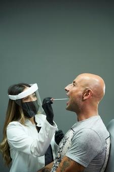 Биолог проводит тест на коронавирус. биолог в перчатках и защитной маске проводит тест на коронавирус у человека в клинике.