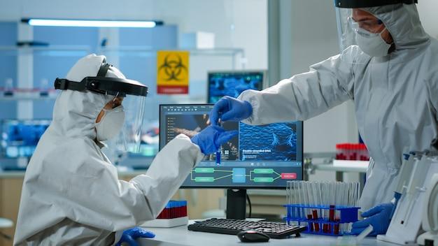 장비를 갖춘 실험실에서 pc에 액체 샘플 입력을 확인하는 ppe 정장을 입은 생물학자. 과학 연구를 위한 첨단 화학 도구를 사용하여 의료 실험실에서 백신 진화를 조사하는 팀