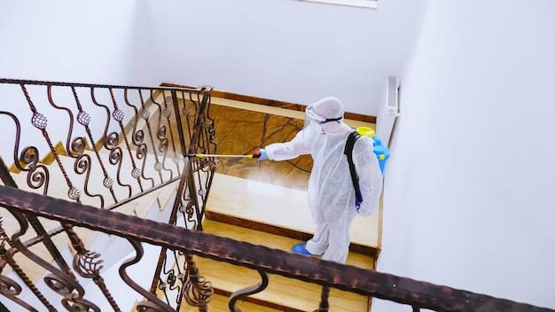 Биолог в полном защитном костюме распыляет дезинфицирующее средство в офисном здании от заражения коронавирусом.