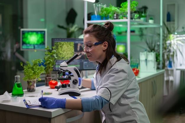 医療用顕微鏡を使用して葉のサンプルを見ている生物学者の科学者