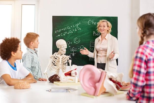 생물학 수업. 해부학 수업을 수행하는 동안 칠판 근처에 서있는 쾌활한 똑똑한 교사