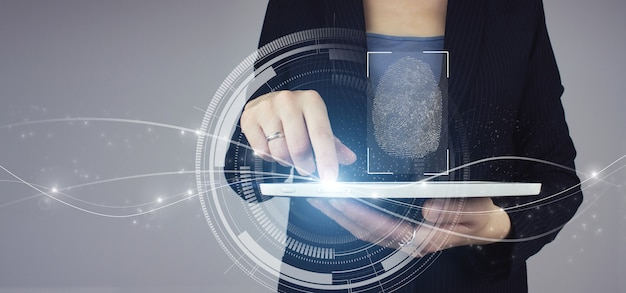 Biometrics identification. white tablet in businesswoman hand with digital hologram fingerprint scan sign on grey background. immersive technology future and cybernetic