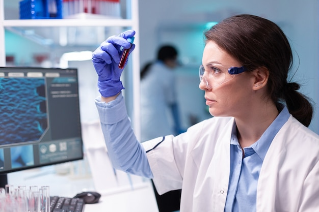 Biotechnologist doctor analysing a blood tube for medical investigation