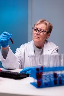 Старший врач биотехнолога анализирует пробирку с кровью для медицинского исследования