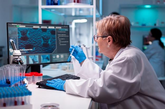 Биотехнолог старший научный сотрудник исследования с пробиркой в фармацевтической лаборатории Premium Фотографии