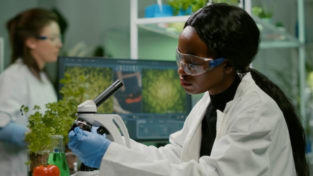 医学の専門知識を研究する生物学的顕微鏡を使用して植物学の緑の葉を調べるバイオテクノロジーの科学者。微生物学科学研究所で有機農業植物を分析する化学者