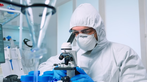 Biotechnology scientist in ppe suit researching dna in laboratory using microscope. team examining virus evolution using high tech for scientific research of vaccine development against covid19