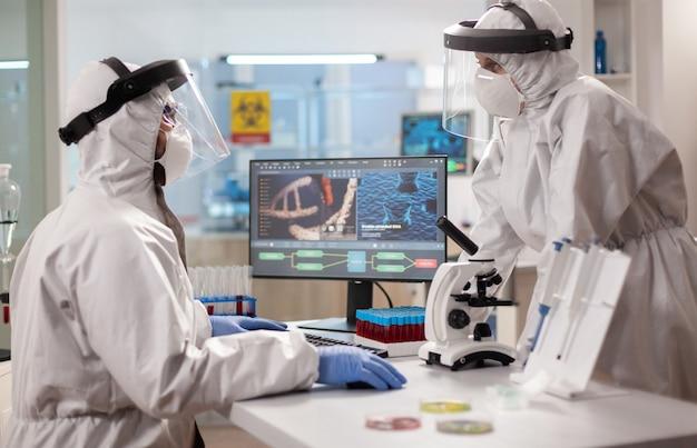 장비 실험실에서 연구하는 ppe 정장을 입고 생명 공학 과학자