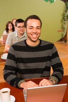 Biracial man at head of row of laptop users
