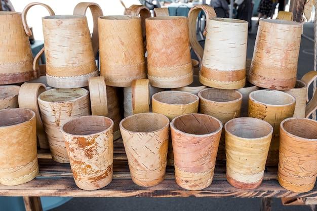 자작나무 껍질로 만든 러시아 민속 공예품 박람회에서 자작나무 껍질 안경과 머그를 판매합니다.